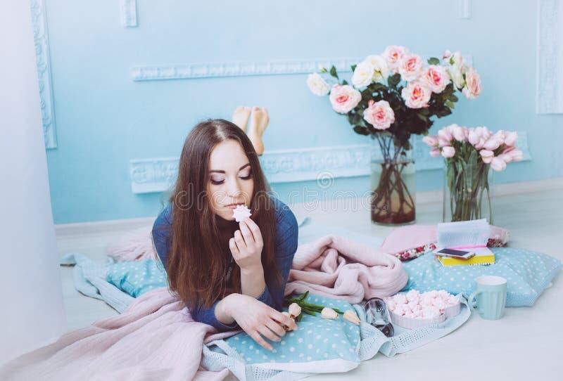 Bella ragazza che si trova sul pavimento e che mangia i macarons Fiori del tulipano sulla mattina blu del fondo della parete in p fotografia stock