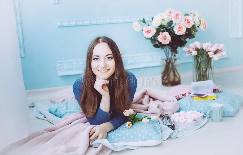 Bella ragazza che si trova sul pavimento e che sorride, con i fiori del tulipano sulla mattina blu del fondo della parete in prim fotografie stock