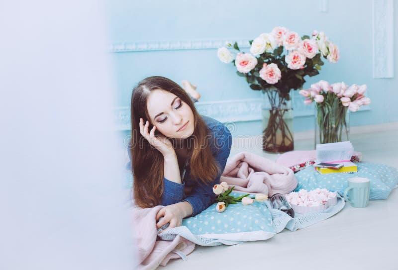 Bella ragazza che si trova sul pavimento e che sorride, con i fiori del tulipano sulla mattina blu del fondo della parete in prim fotografia stock
