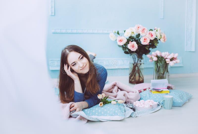 Bella ragazza che si trova sul pavimento e che sorride, con i fiori del tulipano sulla mattina blu del fondo della parete in prim immagine stock libera da diritti