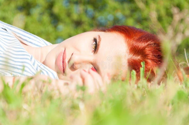 Bella ragazza che si trova sull'erba che sembra felice immagine stock libera da diritti