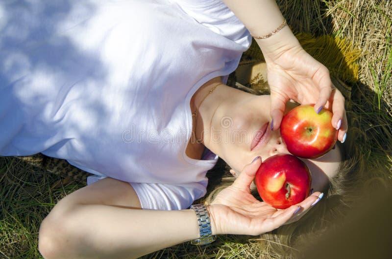 Bella ragazza che si trova sull'erba L'umore divertente, ha coperto il suo fronte di mele fotografia stock