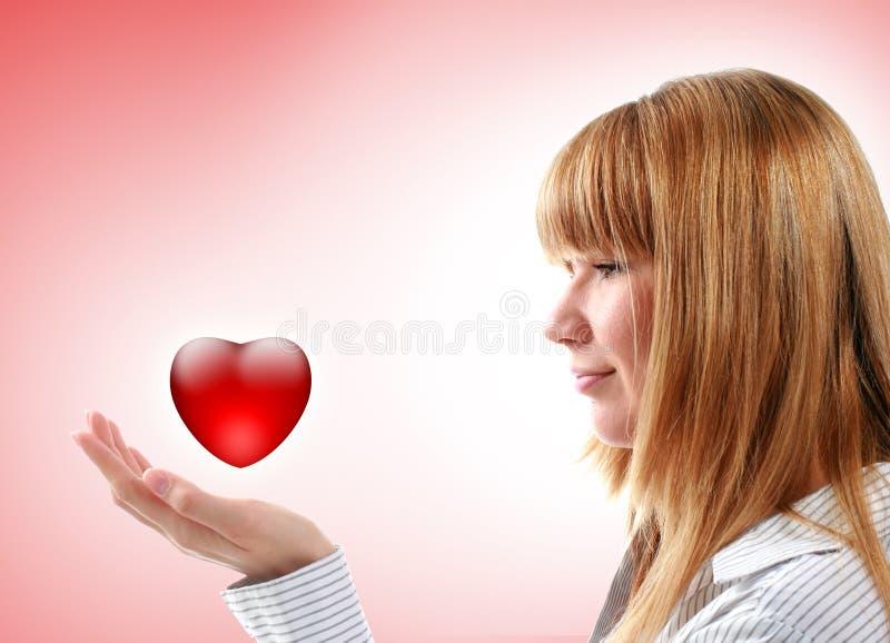 Bella ragazza che tiene cuore rosso. immagine stock