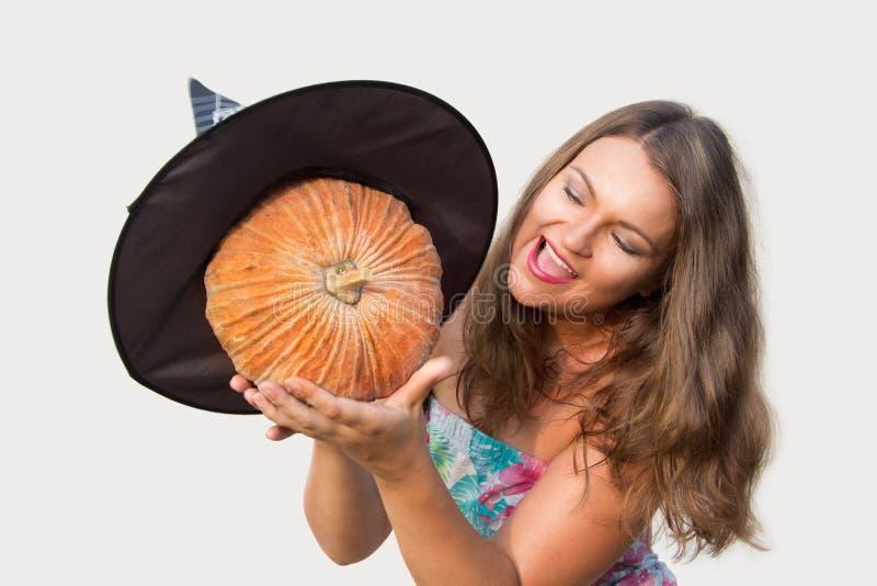 Bella ragazza che tiene la zucca di Halloween con il cappello della strega immagine stock