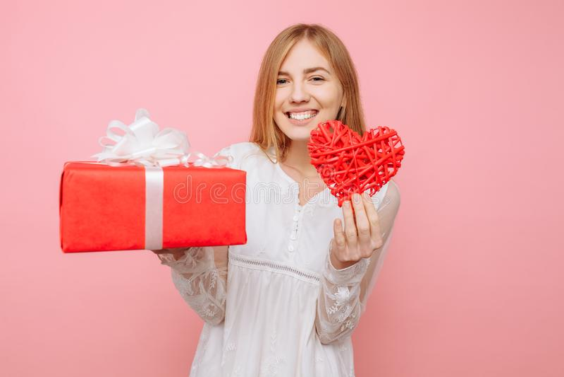 Bella ragazza che tiene un cuore rosso, la scatola di regalo e del biglietto di S. Valentino in sue mani, su un fondo rosa Giorno fotografia stock libera da diritti