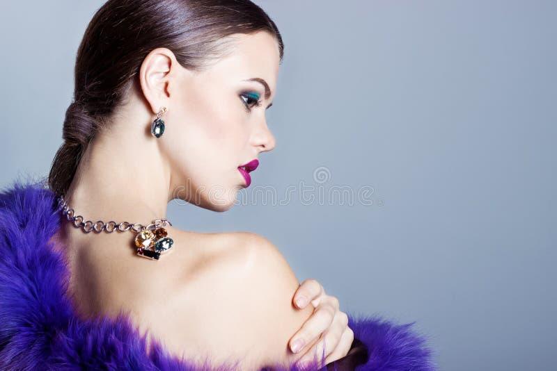 Bella ragazza con bei gioielli costosi alla moda, collana, orecchini, braccialetto, anello, filmante nello studio immagine stock