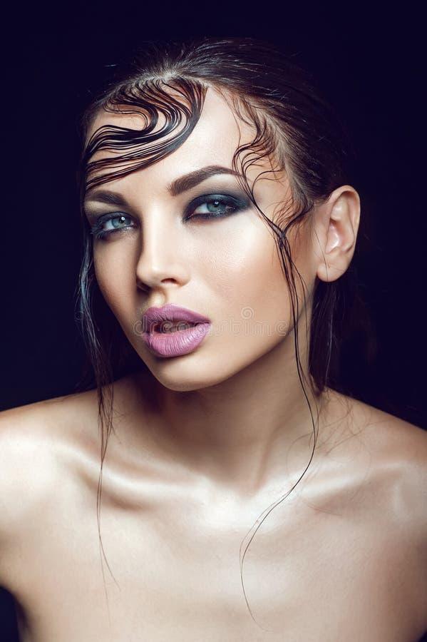 Bella ragazza con capelli bagnati e trucco perfetto di sera sui precedenti neri fotografia stock libera da diritti