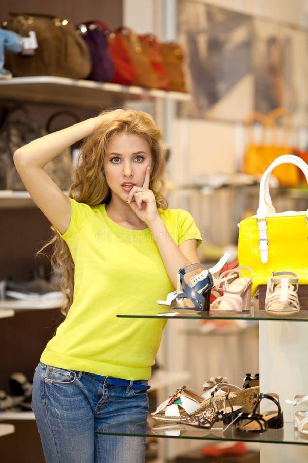 Bella ragazza con capelli bianchi lunghi in un deposito delle scarpe e delle borse immagine stock libera da diritti