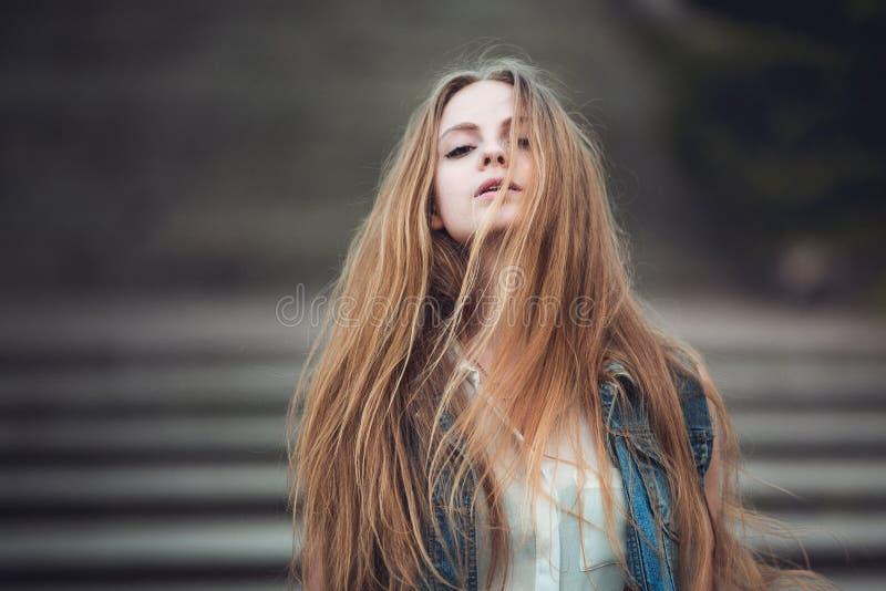 Bella ragazza con capelli biondi lunghi che soffiano dal vento Immagine tonificata fotografia stock