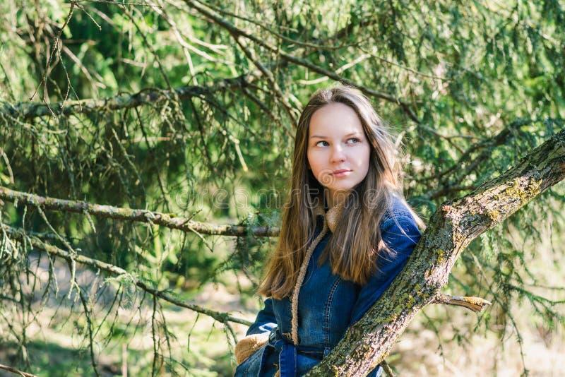 Bella ragazza con capelli biondi lunghi in un rivestimento blu del denim in una foresta verde un giorno di molla soleggiato immagini stock libere da diritti