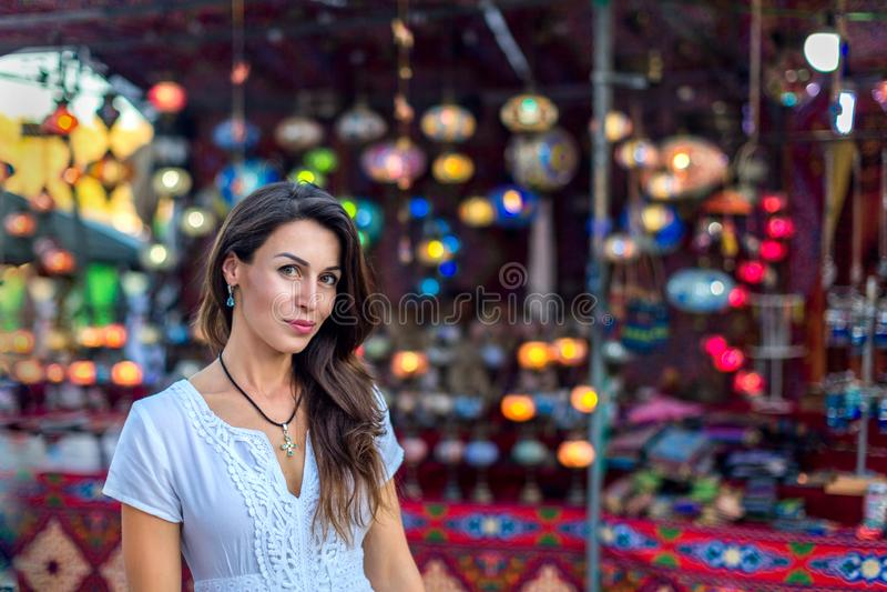Bella ragazza con capelli lunghi in un vestito bianco su un fondo delle lampade etniche marocchine orientali d'ardore ad un merca fotografia stock libera da diritti