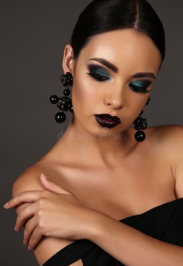Bella ragazza con capelli scuri con trucco esagerato luminoso ed il gioiello fotografia stock libera da diritti