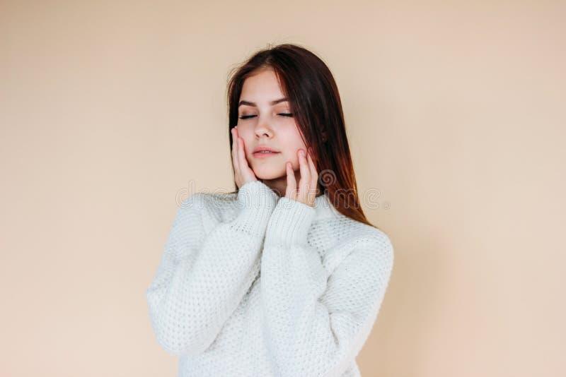 Bella ragazza con gli occhi di chiusura, la pelle pulita ed i capelli lunghi scuri in maglione bianco accogliente su fondo beige immagini stock libere da diritti