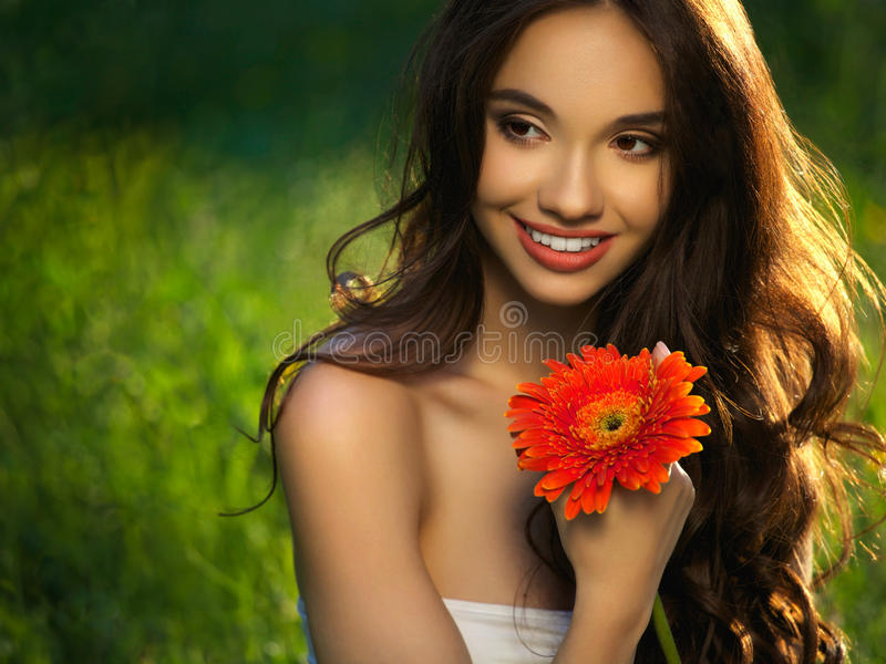 Bella ragazza con i fiori rossi. Bello Woman Face di modello. fotografia stock libera da diritti