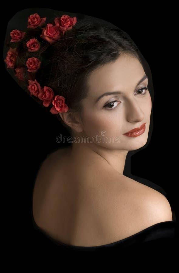 Bella ragazza con i fiori rossi in capelli fotografia stock libera da diritti