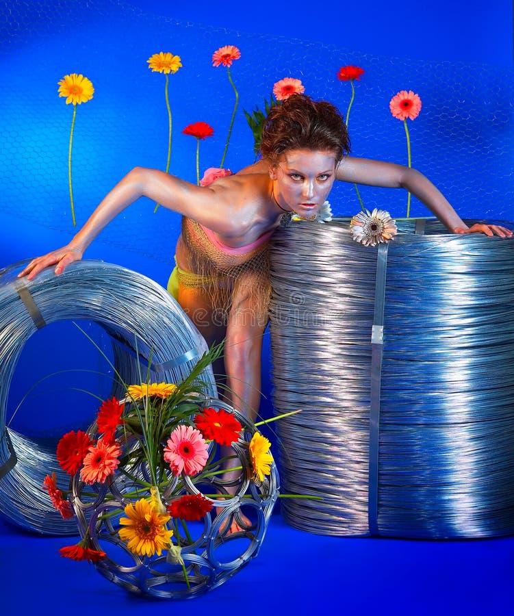 Bella ragazza con i rulli ed i fiori del collegare fotografia stock libera da diritti