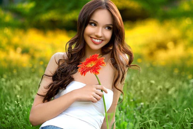 Bella ragazza con il fiore della gerbera fotografia stock