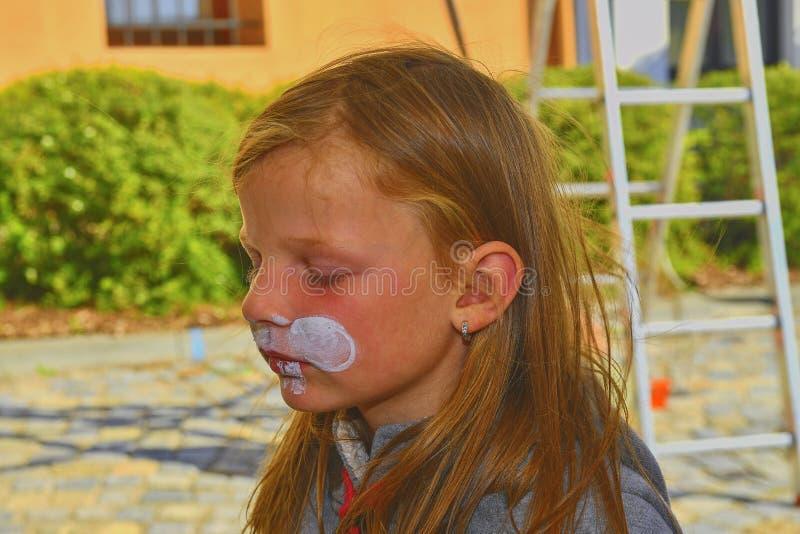 Bella ragazza con il fronte dipinto come un coniglio Pittura del fronte sul fronte del bambino fotografia stock libera da diritti