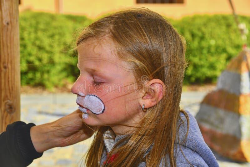 Bella ragazza con il fronte dipinto come un coniglio Pittura del fronte sul fronte del bambino immagini stock