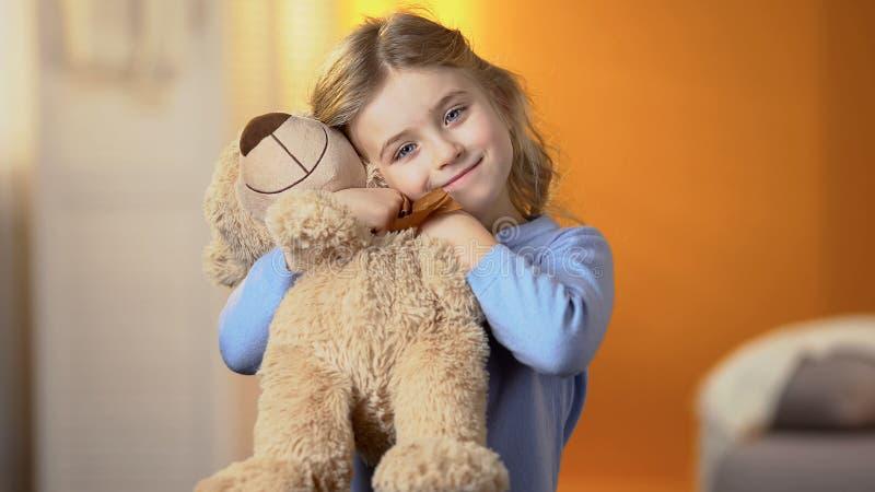 Bella ragazza con il giocattolo favorito dell'orsacchiotto che sorride alla macchina fotografica, infanzia felice fotografia stock libera da diritti