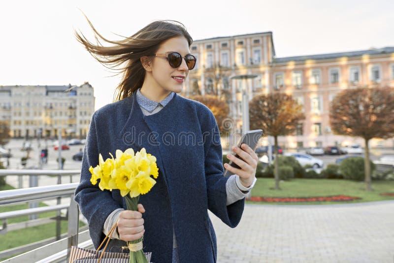 Bella ragazza con il mazzo dei fiori gialli della molla, giovane donna che legge testo con lo smartphone, architettura della citt fotografia stock libera da diritti