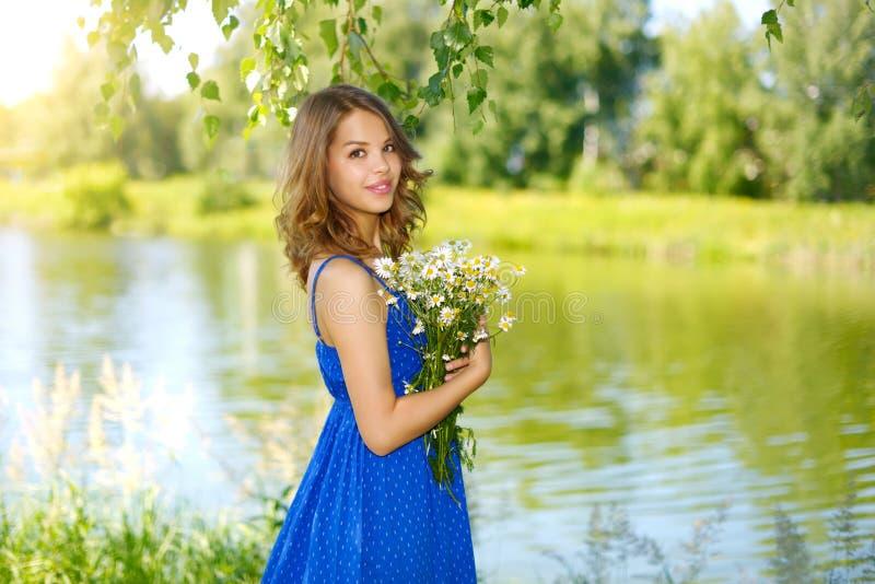 Bella ragazza con il mazzo di camomiles fotografia stock