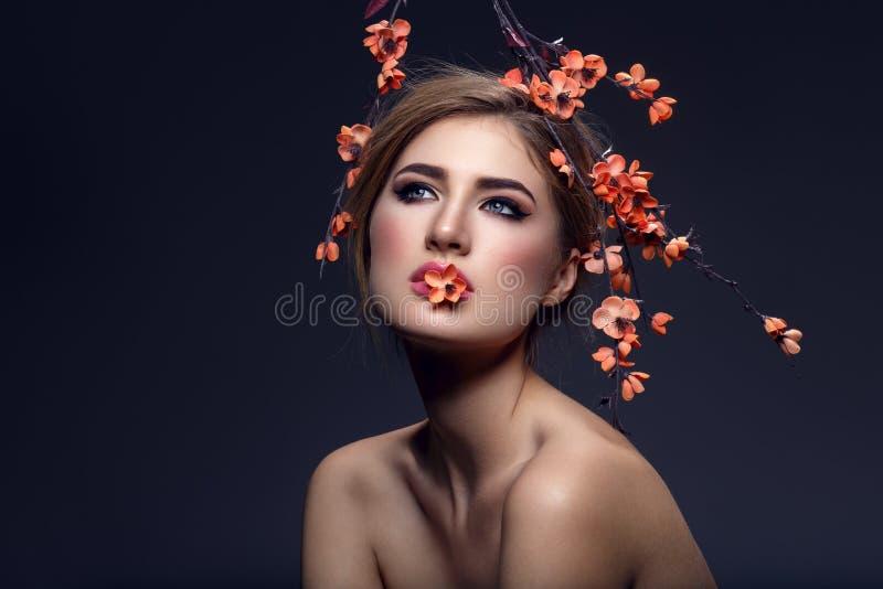 Bella ragazza con il ramo di sakura fotografia stock libera da diritti