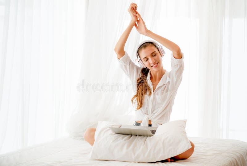 Bella ragazza con il soggiorno bianco della camicia sul letto con il computer portatile ed ascoltare la musica con emozione felic fotografia stock