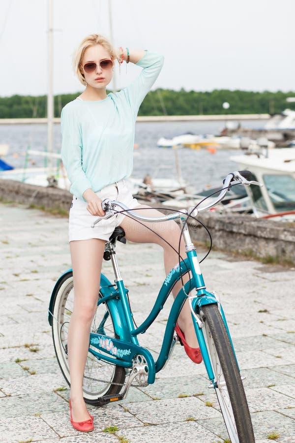 Bella ragazza con la bici della città al pilastro del mare immagini stock libere da diritti