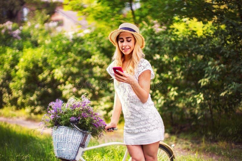 Bella ragazza con la bicicletta d'annata ed i fiori sul fondo della città alla luce solare all'aperto fotografie stock libere da diritti