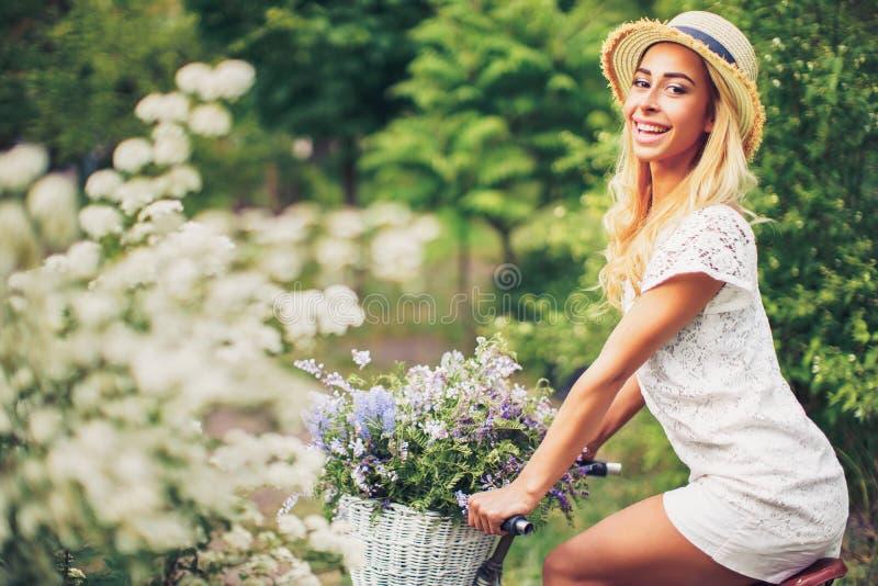 Bella ragazza con la bicicletta d'annata ed i fiori sul fondo della città alla luce solare all'aperto immagine stock libera da diritti