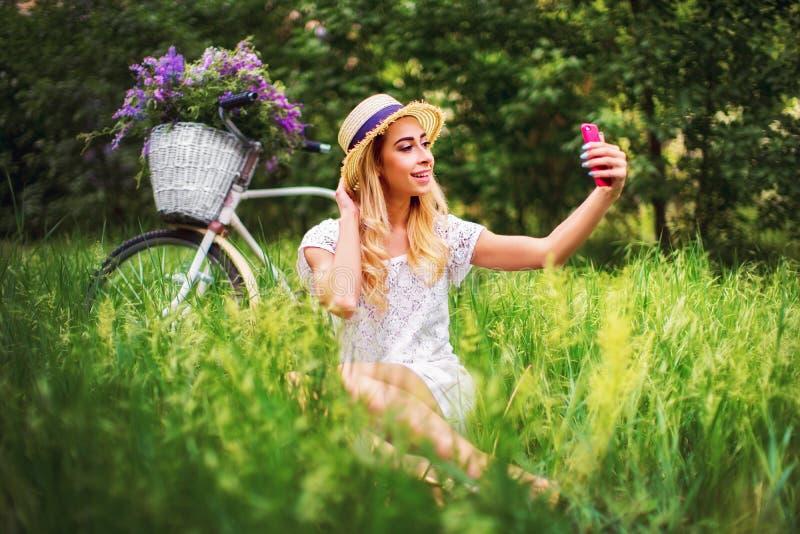 Bella ragazza con la bicicletta d'annata ed i fiori sul fondo della città alla luce solare all'aperto immagine stock