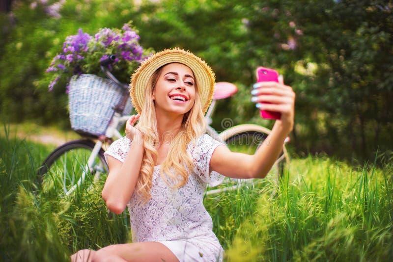 Bella ragazza con la bicicletta d'annata ed i fiori sul fondo della città alla luce solare all'aperto immagini stock libere da diritti