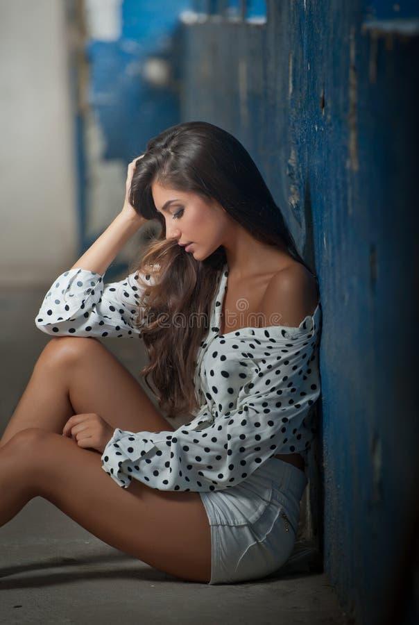 Bella ragazza con la camicia sbottonata che posa, vecchia parete con la pelatura della pittura blu su fondo Seduta abbastanza cas immagini stock