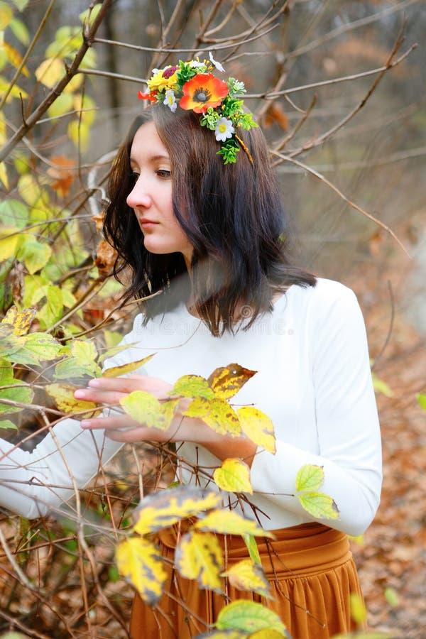 Bella ragazza con la corona del fiore fra i rami dell'autunno all'aperto immagine stock