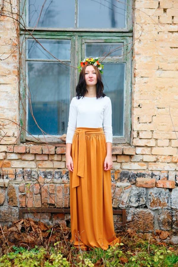 Bella ragazza con la corona del fiore sulla sua finestra di legno vicina capa di vecchia costruzione di mattone immagini stock libere da diritti