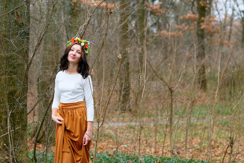 Bella ragazza con la corona del fiore sulla sua testa nella foresta di autunno fotografia stock
