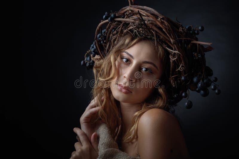Bella ragazza con la corona della vite e l'uva blu fotografie stock