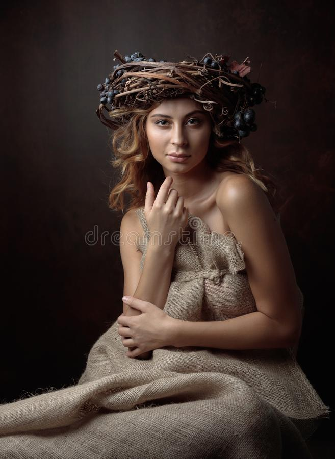 Bella ragazza con la corona della vite e l'uva blu fotografie stock libere da diritti