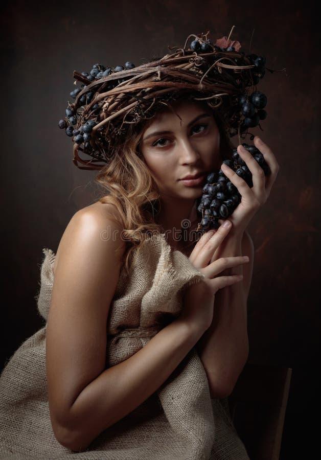 Bella ragazza con la corona della vite e l'uva blu immagine stock