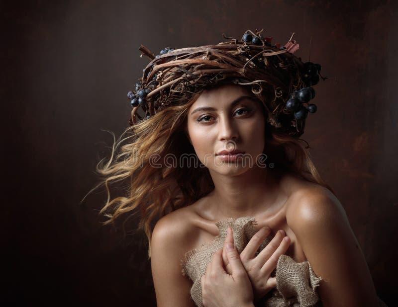 Bella ragazza con la corona della vite e l'uva blu immagini stock libere da diritti