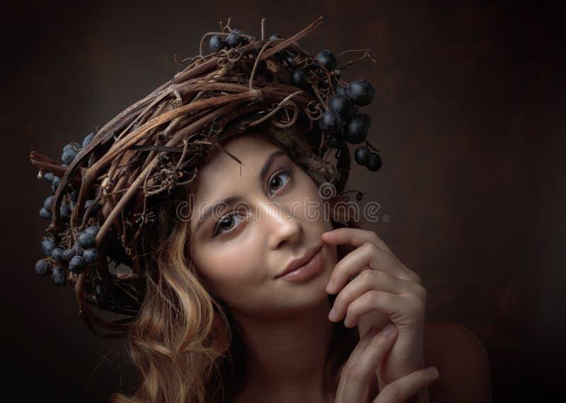 Bella ragazza con la corona della vite e l'uva blu fotografia stock