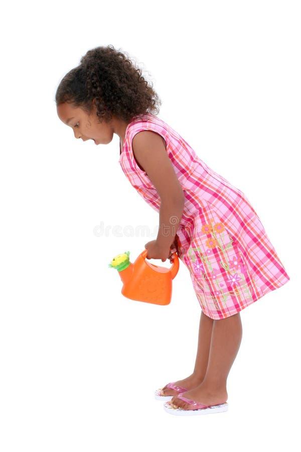Bella ragazza con la latta di innaffiatura del fiore che osserva giù Surpr fotografia stock libera da diritti