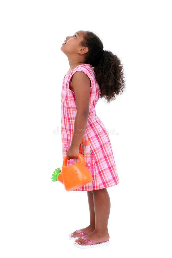 Bella ragazza con la latta di innaffiatura del fiore che osserva in su immagine stock