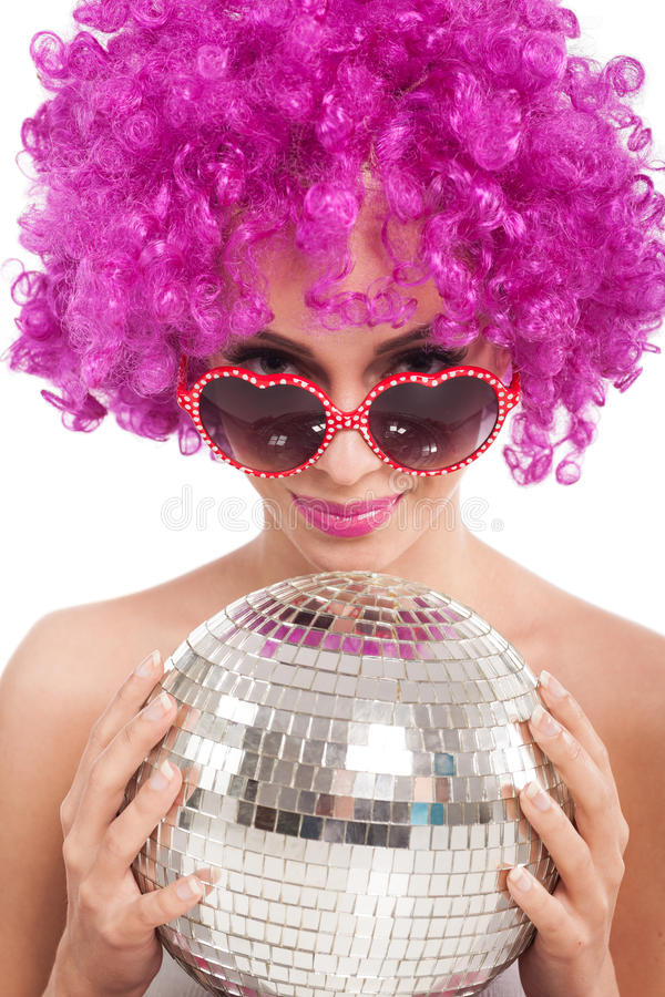 Bella ragazza con la palla rosa della discoteca della tenuta della parrucca, isolata immagine stock