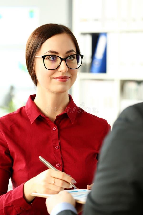 Bella ragazza con la penna d'argento in braccio che firma alcune carte finanziarie immagini stock libere da diritti