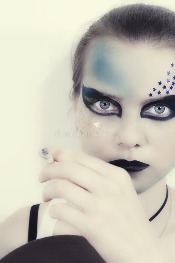 Bella ragazza con la sigaretta nel trucco luminoso fotografie stock