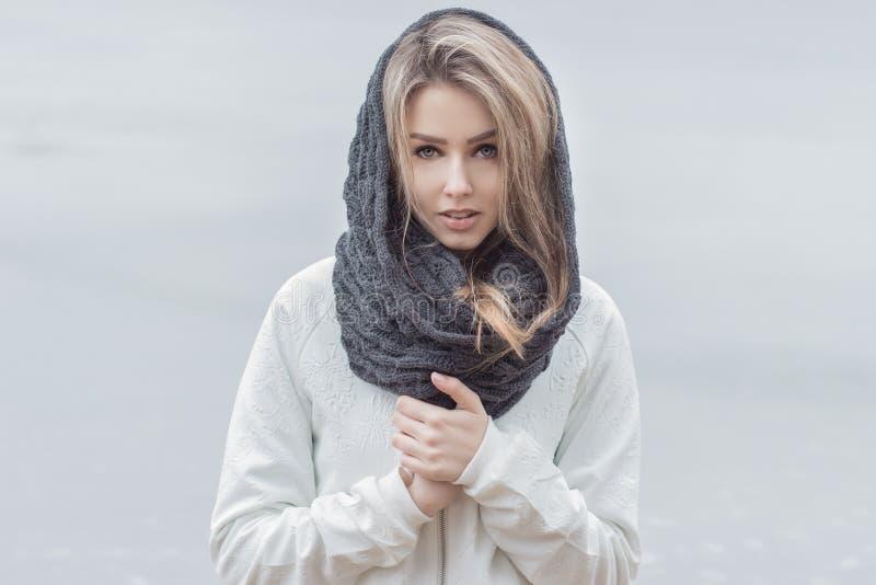 Bella ragazza con le belle labbra in un rivestimento bianco con una sciarpa calda sulla testa in freddo immagini stock libere da diritti