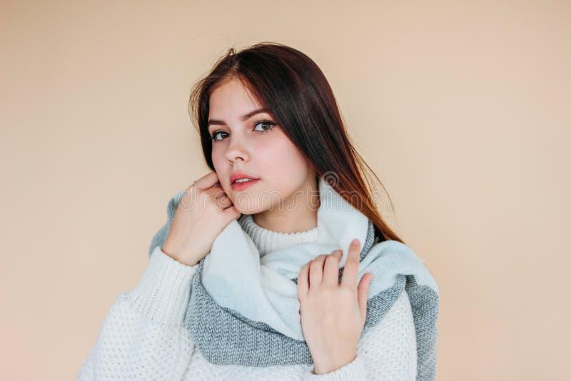 Bella ragazza con pelle pulita e capelli lunghi scuri in maglione bianco accogliente e sciarpa calda su fondo beige immagini stock
