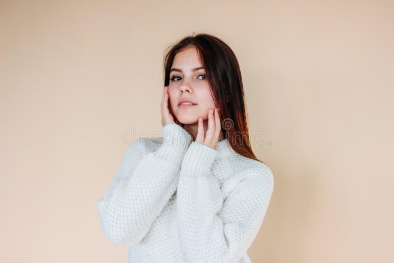 Bella ragazza con pelle pulita e capelli lunghi scuri in maglione bianco accogliente su fondo beige fotografia stock libera da diritti
